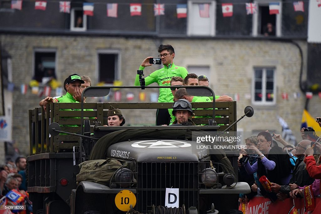 Riders of the USA's Cannondale cycling team take part in a parade aboard an World War II US army jeep during the team presentation ceremony in Sainte-Mere-Eglise, Normandy, on July 30, 2016, two days before the start of the 103rd edition of the Tour de France cycling race. The 2016 Tour de France will start on July 2 in the streets of Le Mont-Saint-Michel and ends on July 24, 2016 down the Champs-Elysees in Paris. / AFP / LIONEL
