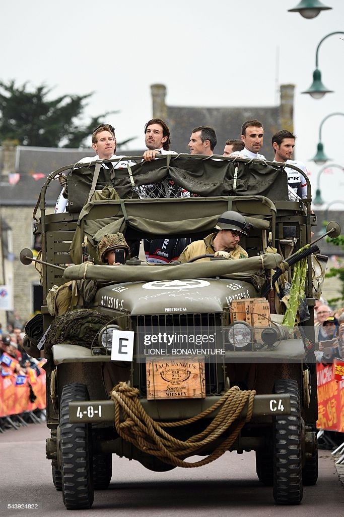 Riders of the USA's Trek - Segafredo cycling team, including Switzerland's Fabian Cancellara (2ndL), take part in a parade aboard an World War II US army jeep during the team presentation ceremony in Sainte-Mere-Eglise, Normandy, on July 30, 2016, two days before the start of the 103rd edition of the Tour de France cycling race. The 2016 Tour de France will start on July 2 in the streets of Le Mont-Saint-Michel and ends on July 24, 2016 down the Champs-Elysees in Paris. / AFP / LIONEL