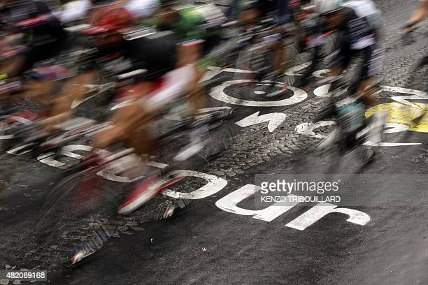 Riders pass over the logo of the Tour de France inscribed in the pavement during the 1095 km twentyfirst and last stage of the 102nd edition of the...