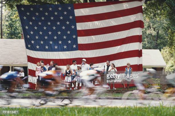 Riders pass spectators and a large stars and stripes flag of the United States during the Men's Individual Road Race on 31 July 1996 during the XXVI...