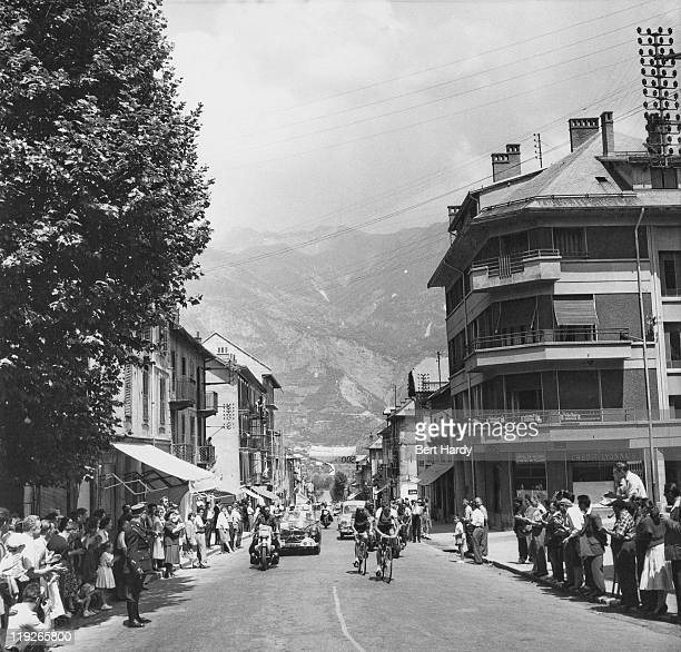 Riders pass through a town in the French Alps during the Tour de France July 1955 Original publication Picture Post 7908 The Tour De France pub 30th...