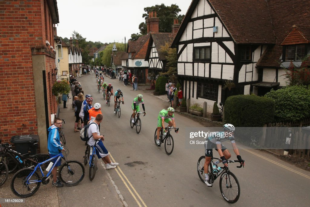Riders pass through the small village of Shere during stage seven of the Tour of Britain from Epsom Racecourse to Guildford on September 21, 2013 in Shere, England. Today's 155km stage is the penultimate one before the race concludes in central London tomorrow. Sir Bradley Wiggins, riding for Team Sky Procycling, currently leads the race beginning today's stage with a 32 second advantage.