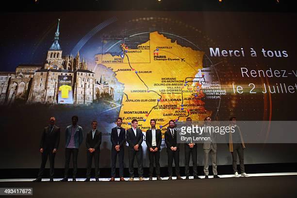 Riders pose in front of the 2016 Tour de France route map at the Palais des Congrès de Paris on October 20 2015 in Paris France