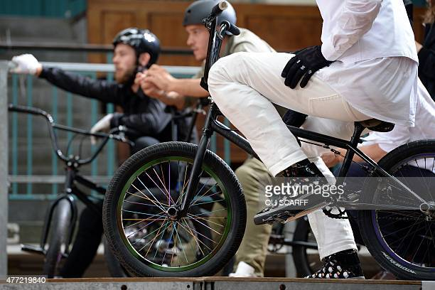 BMX riders prepare to perform in the Seymour Leisure Centre during a presentation for designer Jimmy Choo on the fourth day of the Spring/Summer 2016...