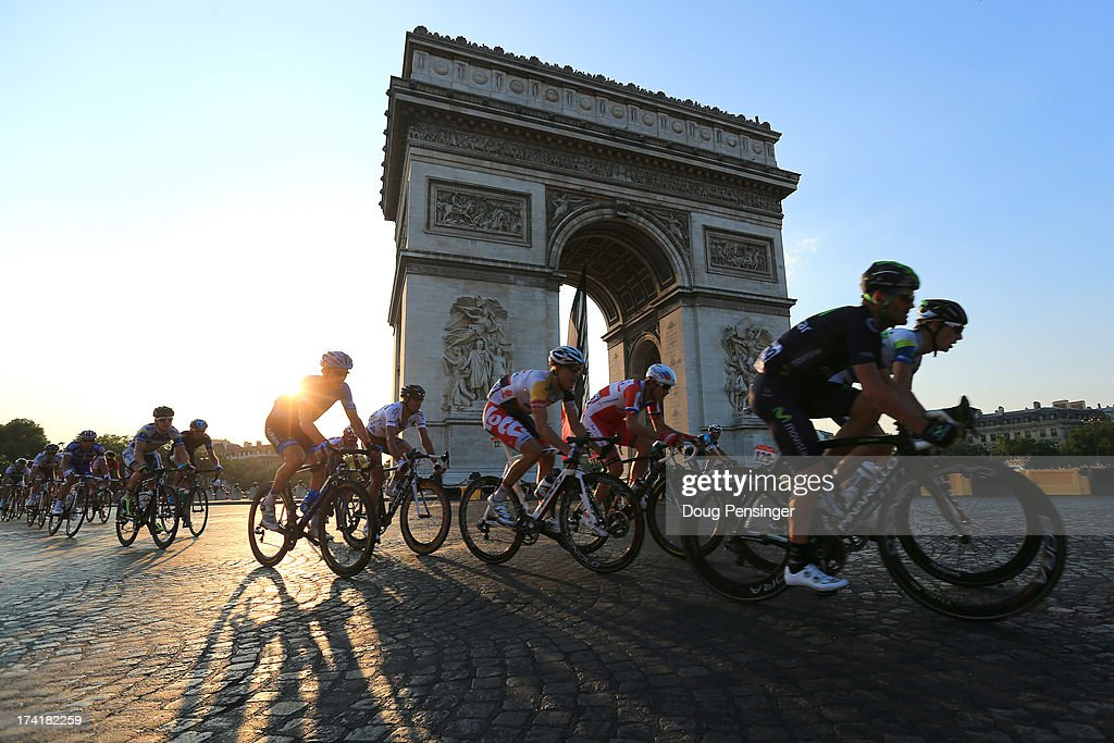Riders round the Arc d'Triomphe during the twenty first and final stage of the 2013 Tour de France, a processional 133.5KM road stage ending in an evening race around the Champs-Elysees, on July 21, 2013 in Paris, France.