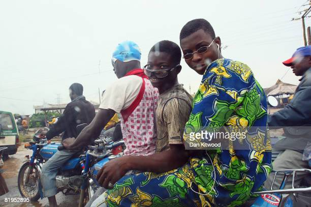 Riders travel on motorbikes as they wautr in congested traffic in central Lagos on July 15 2008 in Lagos Nigeria