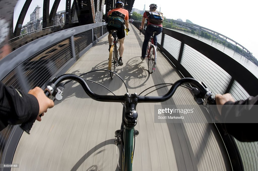 riders view of 2 cyclists commuting across bridge : Stock Photo
