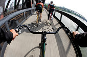riders view of 2 cyclists commuting across bridge