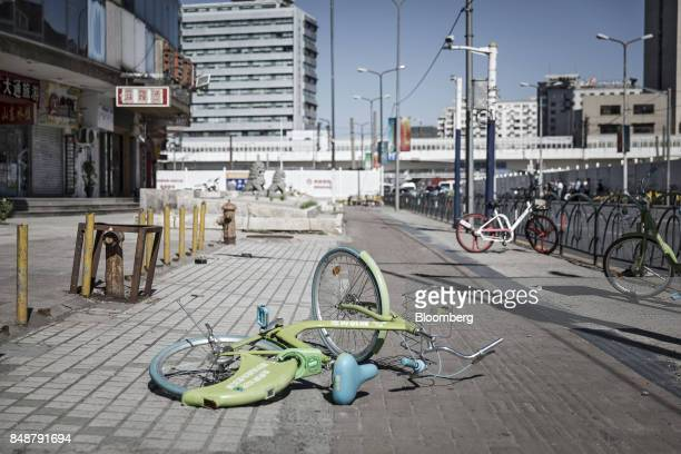 A ridesharing bicycle lies on a sidewalk in Shanghai China on Thursday Sept 12 2017 Across Chinese cities sidewalks are filling up with...