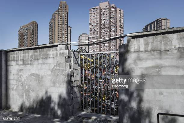 Ridesharing bicycles sit piled up behind a wall in Shanghai China on Thursday Sept 12 2017 Across Chinese cities sidewalks are filling up with...