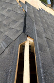 View of a partially shingled house roof, showing the cut-out for a ridge vent at the peak of the roof.