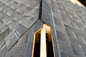 """View of a partially shingled house roof, showing the cut-out for a ridge vent at the peak of the roof.Similar Images:"""