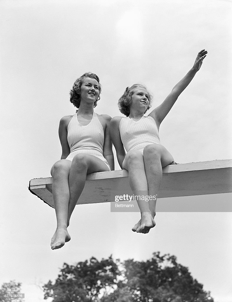 Country club swimming pool Two young women in bathing suits sit on the end of a diving board Undated photograph circa 1950's