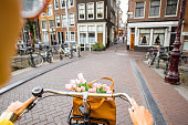 Woman riding a bicycle with bouquet of flowers on the street in Amsterdam city. View on the hands holding helm