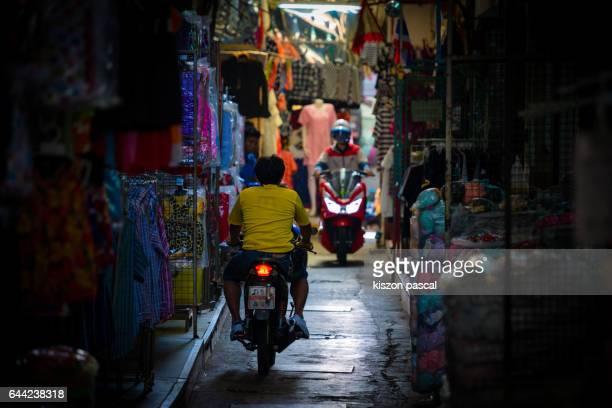 Riding a bike in Market in Bangkok ; Thailand ; Asia