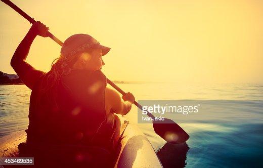 Riding a kayak on sea at sunset