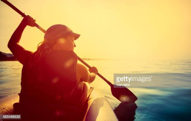 Riding a kayak on sea at sunset
