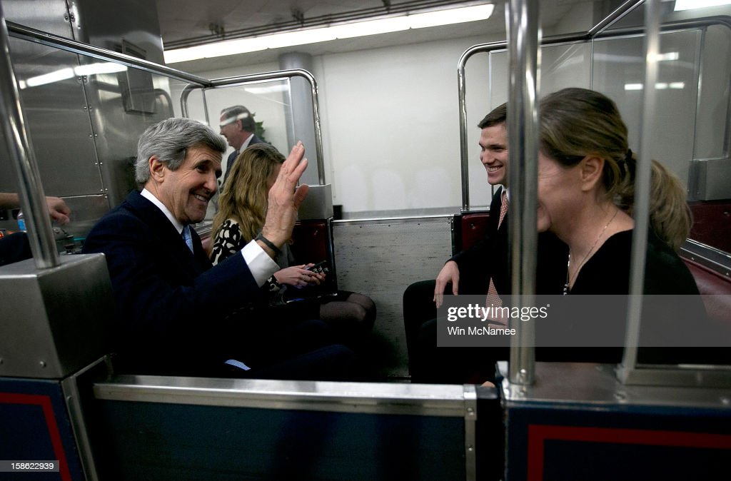 Riding a subway at the U.S. Capitol, Sen. John Kerry (D-MA) (L) waves to supporters congratulating him on his nomination by U.S. President Barack Obama as the next Secretary of State December 21, 2012 in Washington, DC. If confirmed, Kerry will replace retiring Secretary of State Hillary Clinton early in 2013.