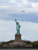Riding atop a 747 shuttle carrier aircraft the space shuttle Enterprise flies past the Statue of Liberty in New York Harbor on April 27 2012 in New...