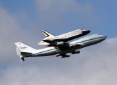 Riding atop a 747 shuttle carrier aircraft the space shuttle Enterprise flies over New York Harbor on April 27 2012 in New York City Enterprise which...
