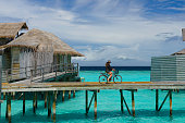 A young adult woman riding a bicycle on pier over a tropical sea.