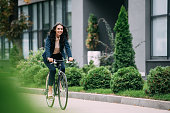 young happy businesswoman riding bicycle