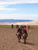 """Young man and women as tourists riding camels by Dunes in Gobi desert in summer time, Hongoran Els, south Mongolia."""