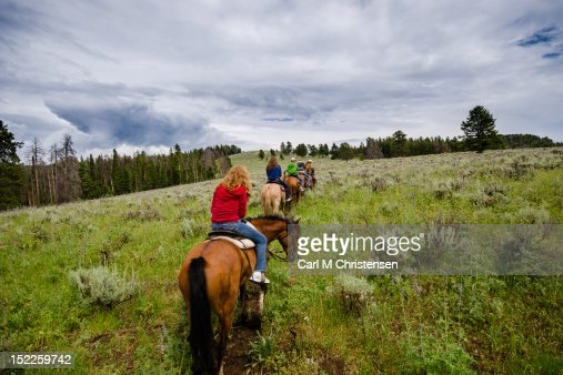 Riding horseback single file in mountains : Stock Photo