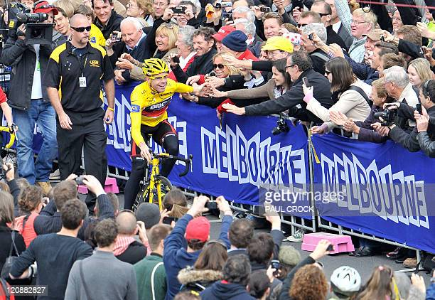 Riding in his winner's yellow jersey Tour de France winner Cadel Evans of Australia is greeted by some of the thousands of fans which lined the...