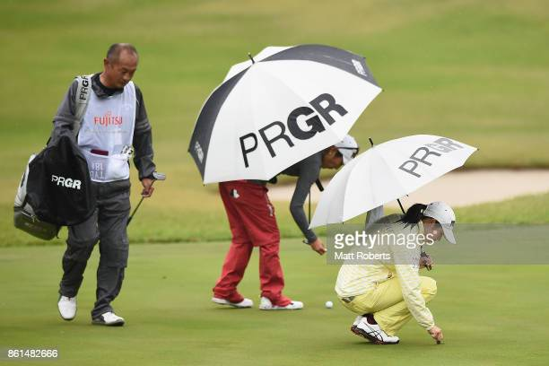 Rie Tsuji and Asako Fujimoto of Japan inspect the green during the final round of the Fujitsu Ladies 2017 at the Tokyu Seven Hundred Club on October...