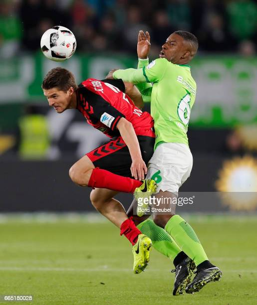 Riechedly Bazoer of VfL Wolfsburg battles for the ball with Aleksandar Ignjovski of Freiburg during the Bundesliga match between VfL Wolfsburg and SC...