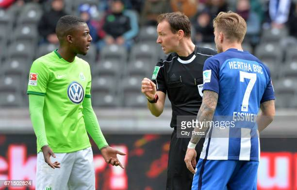 Riechedly Bazoer of VfL Wolfsburg referee Bastian Dankert and Alexander Esswein of Hertha BSC during the game between Hertha BSC and dem VfL...