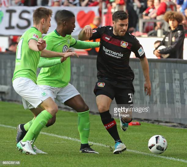 Riechedly Bazoer of Wolfsburg and Kevin Volland of Leverkusen battle for the ball during the Bundesliga match between Bayer 04 Leverkusen and VfL...