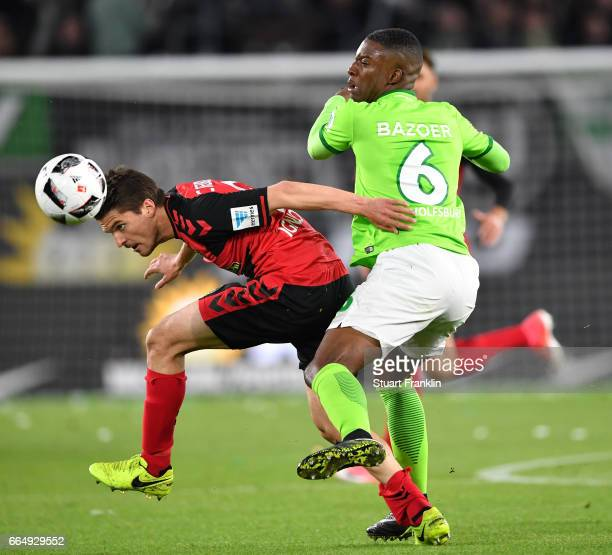 Riechedly Bazoer of Wolfsburg is challenged by Aleksandar Ignjovski of Freiburg during the Bundesliga match between VfL Wolfsburg and SC Freiburg at...