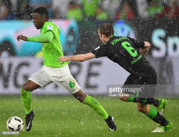 Riechedly Bazoer of Wolfsburg is challenged by Christoph Kramer of Gladbach during the Bundesliga match between VfL Wolfsburg and Borussia...