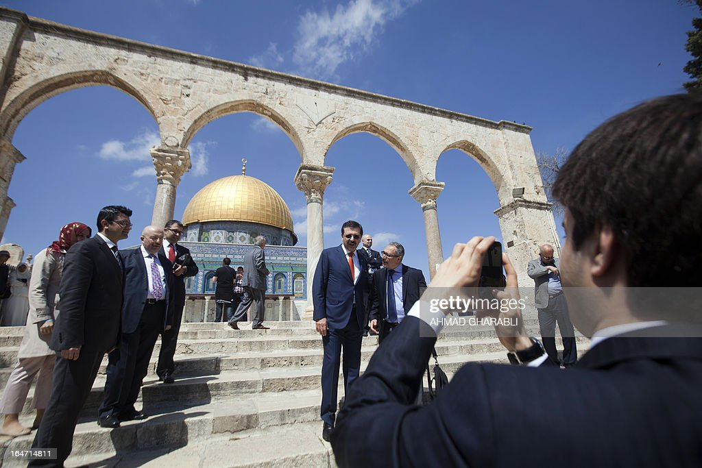 Rifat Hisarciklioglu (C), President of the Union of Chambers & Commodity Exchanges of Turkey (TOBB), poses for a photograph as he walks from Jerusalem's Dome of the Rock mosque during his visit to the Al-Aqsa mosques compound, Islam's third holiest site, on March 27, 2013. US President Barack Obama brokered a tentative reconciliation between Israeli Prime Minister Benjamin Netanyahu and Turkish Prime Minister Recep Tayyip Erdogan during his visit to Israel earlier this month, with Netanyahu apologising for a 2010 raid on a Gaza-bound aid flotilla during which Israeli soldiers killed nine Turks during the raid.