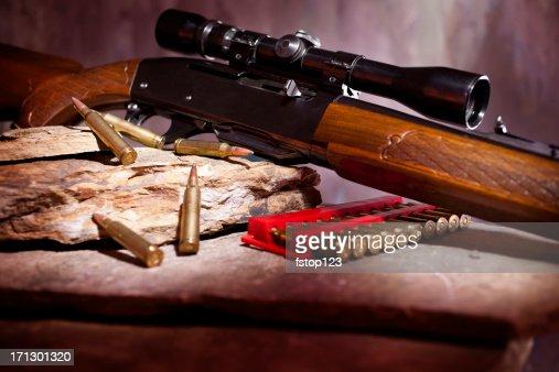 Rifle with sight and ammunition on rock shelf
