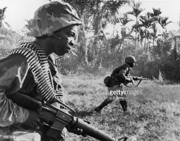 US riflemen from the 173rd Airborne Brigade charge toward Viet Cong positions holding machine guns in a wooded area of War Zone D during the Vietnam...
