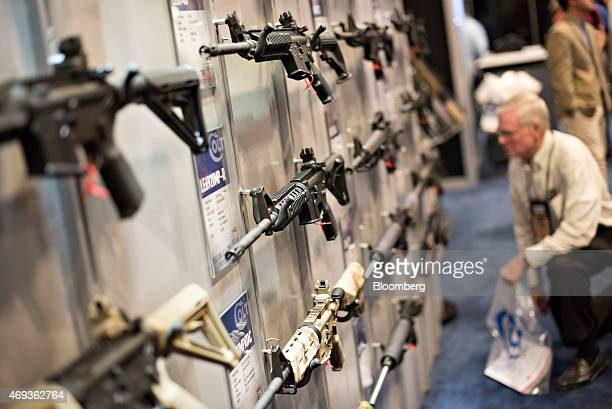 Rifles hang on display in the Colt's Manufacturing Co booth on the exhibition floor of the 144th National Rifle Association Annual Meetings and...