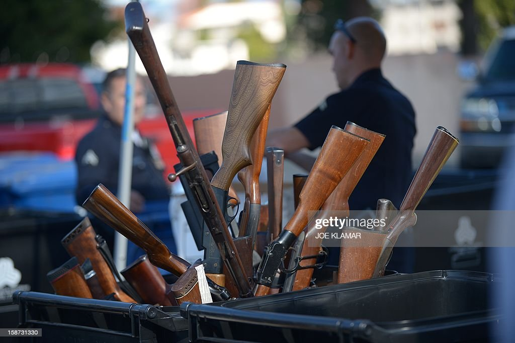 Rifles stick out of a trash bin collected during the LAPD Gun Buyback Program event in Van Nuys area, north of Los Angeles, on December 26, 2012. By noon LAPD collected more then 420 handguns, rifles and shotguns such as TEC-9, Assault rifle, Uzi, WWI rifle. Apart from it, there are 16 assault weapons and some vintage weapons. One is dated 1895. AFP PHOTO / JOE KLAMAR