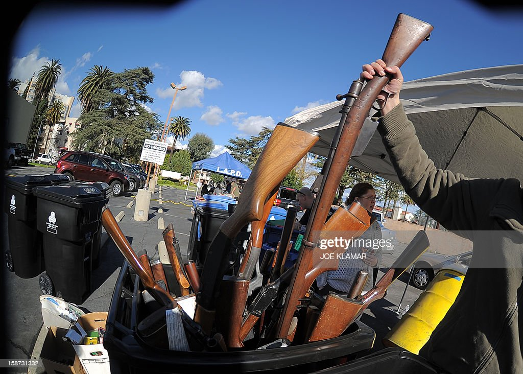 Rifles stick out of a trash bin collected during the LAPD Gun Buyback Program event in Van Nuys area, north of Los Angeles, on December 26, 2012. By noon LAPD collected more then 420 handguns, rifles and shotguns such as TEC-9, Assault rifle, Uzi, WWI rifle. Apart from it, there are 16 assault weapons and some vintage weapons. One is dated 1895.