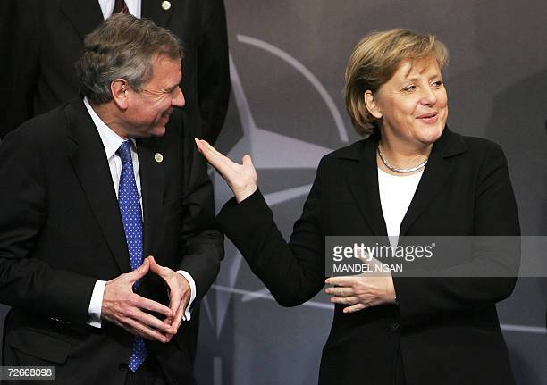 NATO Secretary General Jaap de Hoop Scheffer shares a laugh with German Chancellor Angela Merkel while posing for the NATO leader's family photo 29...