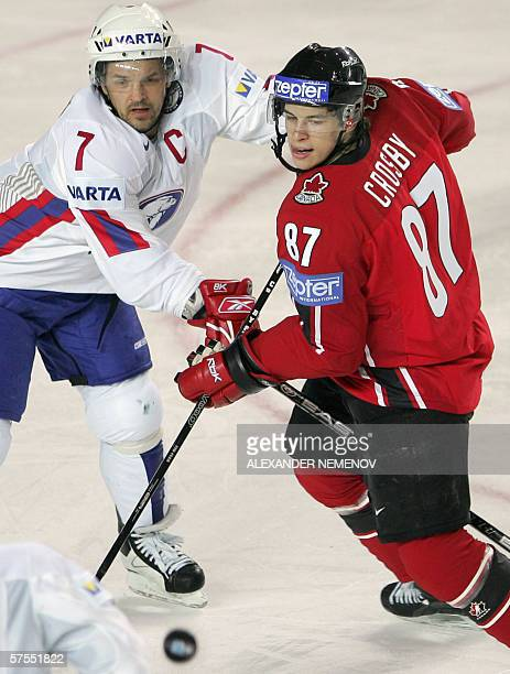 Norway captain Tommy Jakobsen fights for the puck with Canadian Sidney Crosby during their preliminary round group D match of the Internetional Ice...