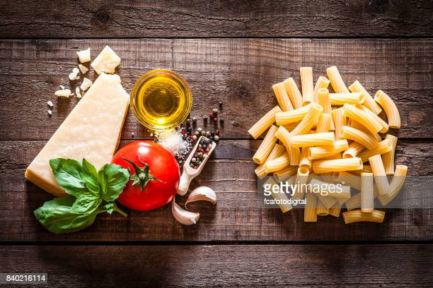 Rigatoni pasta with ingredients on rustic wooden table