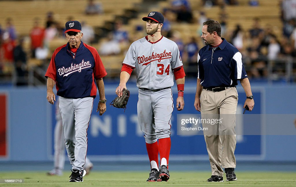 Right fielder Bryce Harper of the Washington Nationals walks off the field with trainer Lee Kuntz and manager Davey Johnson as he bleeds from the...