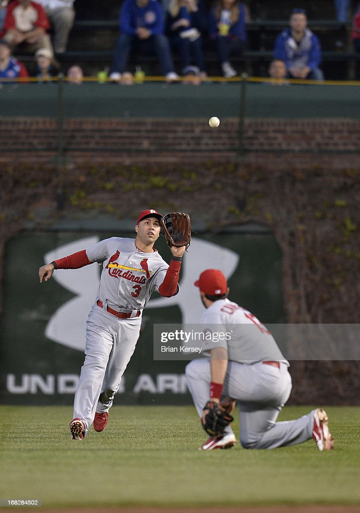 Right fielder <a gi-track='captionPersonalityLinkClicked' href=/galleries/search?phrase=Carlos+Beltran&family=editorial&specificpeople=167108 ng-click='$event.stopPropagation()'>Carlos Beltran</a> #3 of the St. Louis Cardinals (L) catches a soft fly ball hit by Travis Wood #37 of the Chicago Cubs as second baseman Matt Carpenter #13 gets out of the way during the third inning on May 7, 2013 at Wrigley Field in Chicago, Illinois.