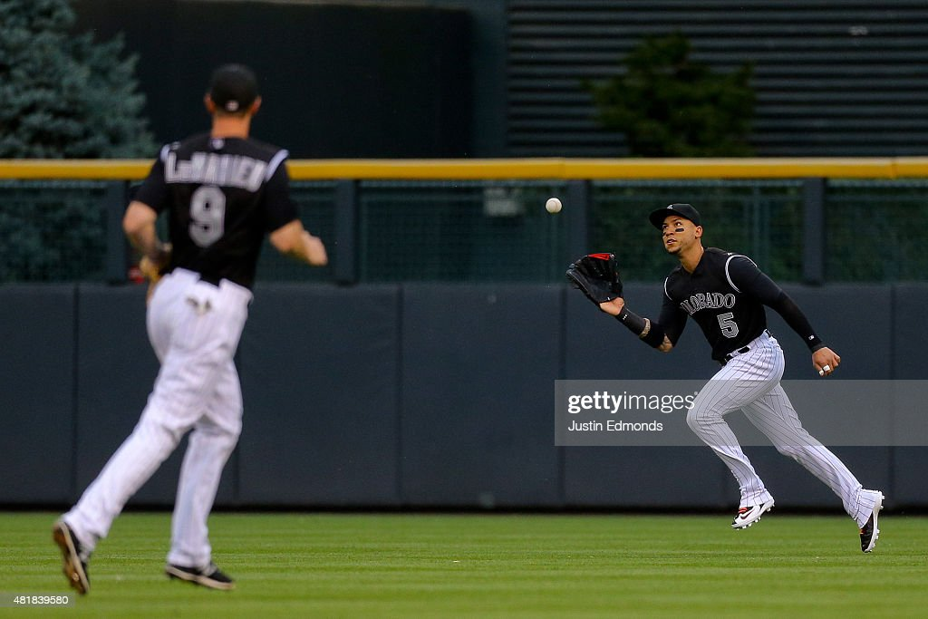 Right fielder Carlos Gonzalez #5 of the Colorado Rockies makes a catch on the run for the third out of the first inning as <a gi-track='captionPersonalityLinkClicked' href=/galleries/search?phrase=DJ+LeMahieu&family=editorial&specificpeople=5940806 ng-click='$event.stopPropagation()'>DJ LeMahieu</a> #9 looks on against the Cincinnati Reds at Coors Field on July 24, 2015 in Denver, Colorado.
