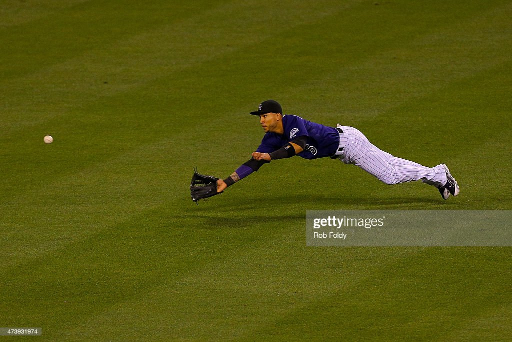 Right fielder Carlos Gonzalez #5 of the Colorado Rockies makes a diving catch for the first out of the ninth inning against the Philadelphia Phillies at Coors Field on May 18, 2015 in Denver, Colorado. The Phillies defeated the Rockies 4-3.