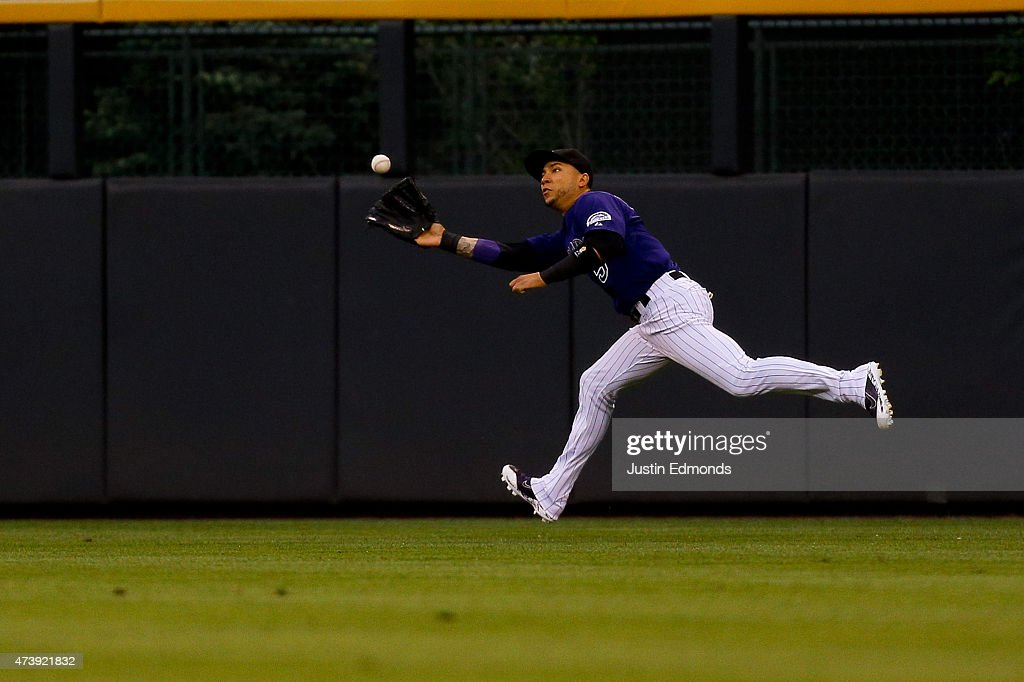 Right fielder <a gi-track='captionPersonalityLinkClicked' href=/galleries/search?phrase=Carlos+Gonzalez+-+Amerikansk+basebollspelare&family=editorial&specificpeople=7204259 ng-click='$event.stopPropagation()'>Carlos Gonzalez</a> #5 of the Colorado Rockies makes a running catch for the first out of the first inning against the Philadelphia Phillies at Coors Field on May 18, 2015 in Denver, Colorado.