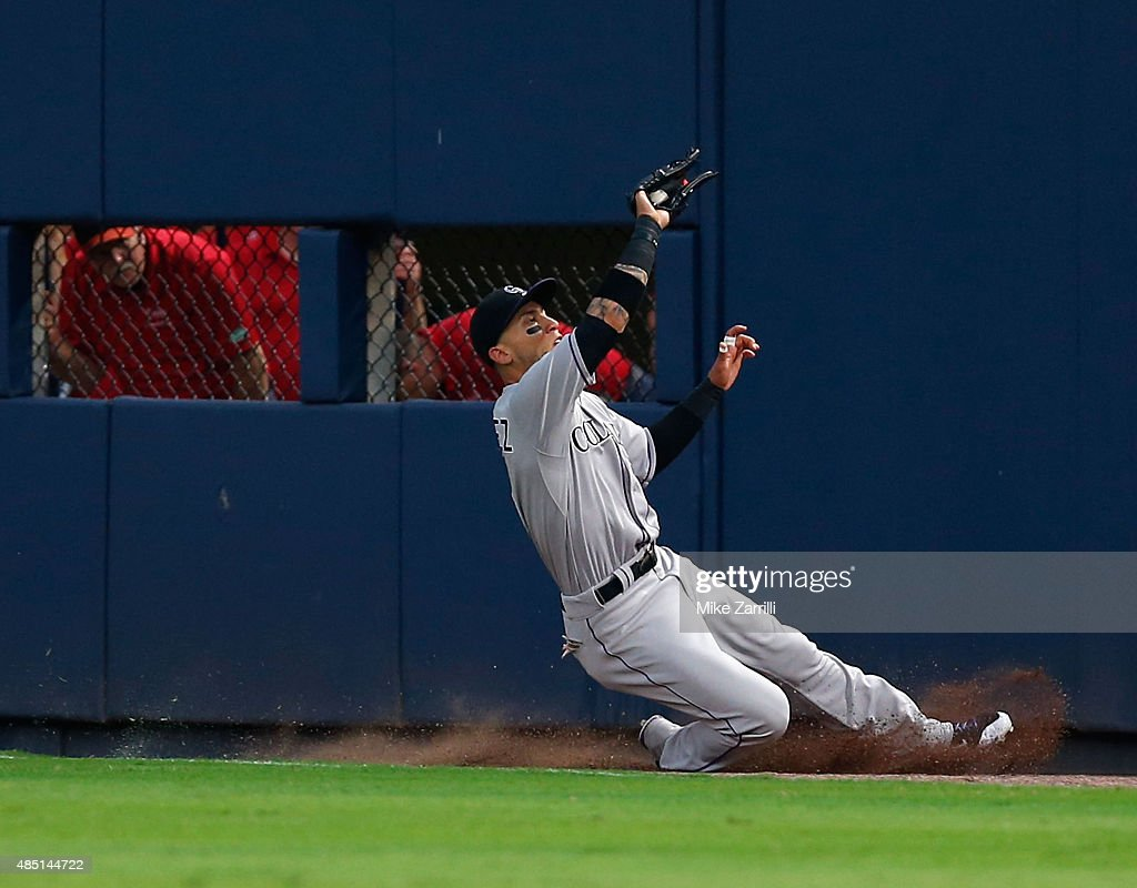 Right fielder <a gi-track='captionPersonalityLinkClicked' href=/galleries/search?phrase=Carlos+Gonzalez+-+Amerikansk+basebollspelare&family=editorial&specificpeople=7204259 ng-click='$event.stopPropagation()'>Carlos Gonzalez</a> #5 of the Colorado Rockies makes a sliding catch in the third inning during the game against the Atlanta Braves at Turner Field on August 24, 2015 in Atlanta, Georgia.